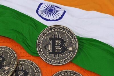 3d rendering of a metallic bitcoin over an indian flag